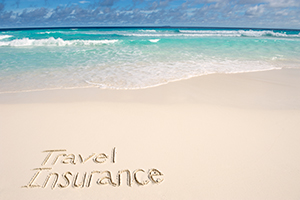 'Travel insurance' written in the sand